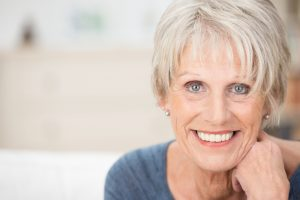 Close up facial portrait of a beautifSenior woman enjoying her all-on-four implant-retained denture.